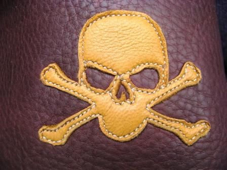 gold skull crossbones leather artwork